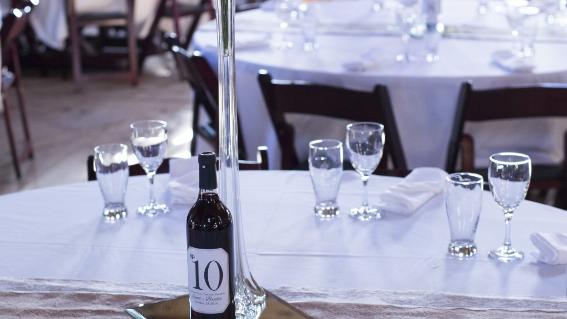 Custom wine bottle centerpiece at wedding reception